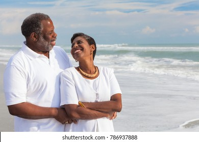 Happy romantic senior African American man and woman couple looking at each other on a deserted tropical beach