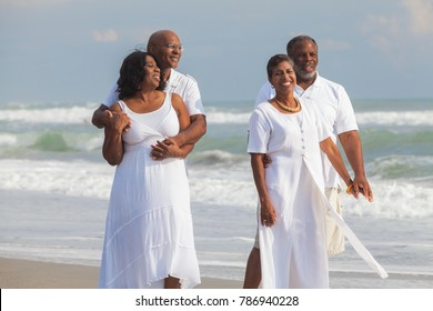 Happy romantic senior African American men and women couples walking on a deserted tropical beach
