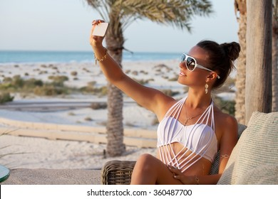 Happy Romantic Woman Enjoying Beautiful Sunset at the Beach, taking selfie. Outdoors lifestyle portrait. Summer luxury vacation.