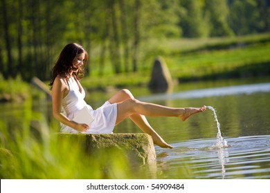 Happy romantic woman sitting by lake splashing water, wearing white dress