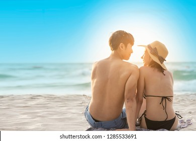 Happy Romantic Young Asian Couple Enjoying Beautiful Sunset Lying on the Beach. Cheerful Couple Make Heart With Sunset Time. Travel Vacation, Valentine, Love, Lifestyle Concept.