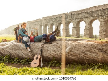 Happy romantic young couple backpackers tourists with guitar sitting lying on a log trunk reading map guide in front of ancient roman aqueduct ruins park in rome.