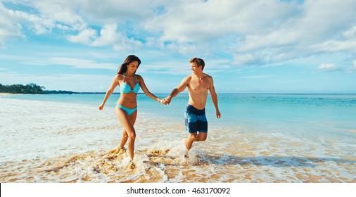Schönes romantisches Paar, das am Strand spaziert und spielt