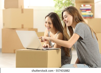 Happy roommates searching on line with a laptop on a cardboard box and moving home sitting on the floor of the living room