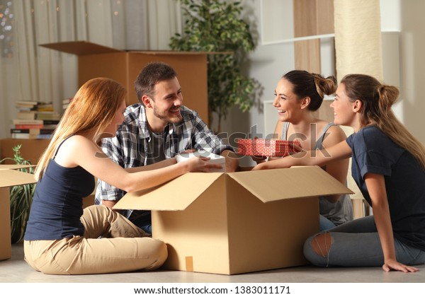 Happy roommates unboxing belongings moving home sitting on the floor in the night