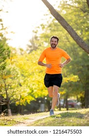 Happy runner in sportswear running training for Marathon outside in park at sunset on beautiful summer day in Sports Healthy lifestyle and Jogging Cross Country Training Workout Outdoors concept.