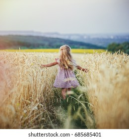 Happy running girl on a wheat field at sunset