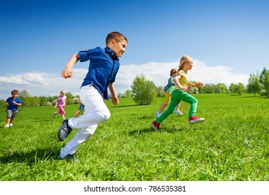 Happy running kids in the green park during daytime and sunny beautiful weather