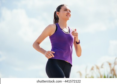 Happy running smiling woman in purple t-shirt and on blue sky background. Workout outdoor. Sport