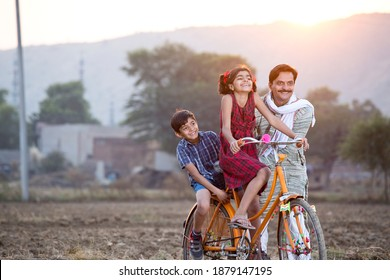 Happy rural Indian farmer with children riding on bicycle