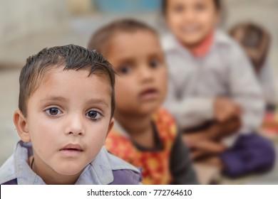 Happy Rural Kids sitting on floor of school, looking at camera