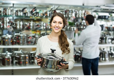 happy russian couple chooses pans in shop cookware. focus on girl