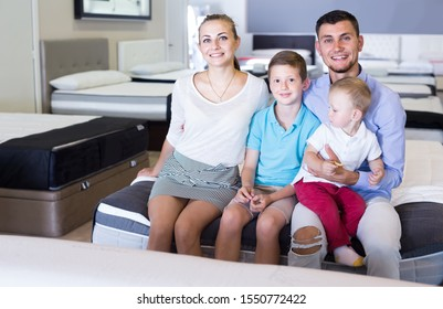 Happy russian family of four sitting on bed in furniture salon, choosing right mattress