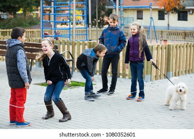 happy russian kids skipping on chinese jumping elastic rope in yard