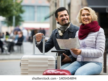 happy russian mature couple with suitcases, camera and map outdoors. focus on woman