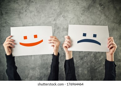 Happy and sad face emoticons, two women holding papers with happiness and sadness emoji.
