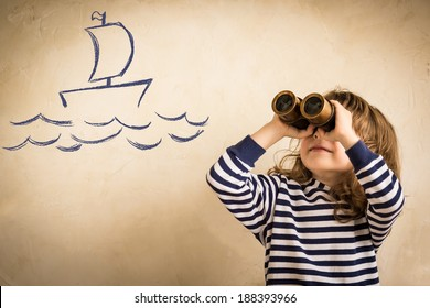 Happy sailor kid playing indoors. Smiling child look at drawing ship. Travel and adventure concept. Summer vacation