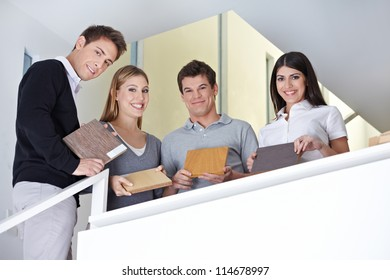 Happy sales team showing wood samples in office