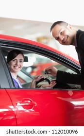 Happy salesman giving car keys to a woman in a car shop