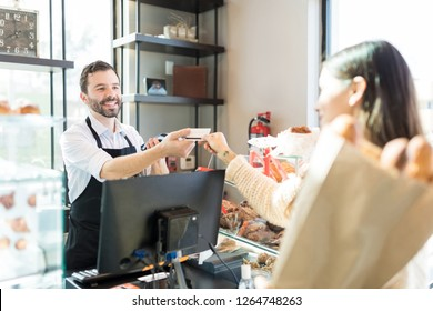 Happy salesman receiving credit card from customer in bakery