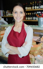 happy saleswoman cheese in grocery store