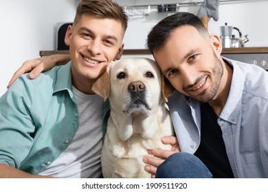happy same sex family smiling near labrador at home