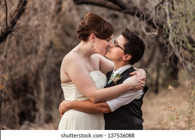 Happy same sex newlyweds kissing in the woods