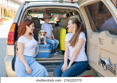Happy same-sex family going on a car trip around the country. Lesbian couple with son and dog are loading luggage in the trunk and is ready for summer vacation. Independent travel.