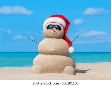 Happy sandy snowman in Christmas Santa Claus hat and sunglasses at sunny ocean beach, New Year holiday destinations concept for travel to hot south countries