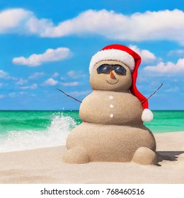 Happy sandy snowman in red Santa hat and sunglasses at tropical ocean sunny beach against waves splashes. New Year and Christmas traveling destinations concept for tropical vacation