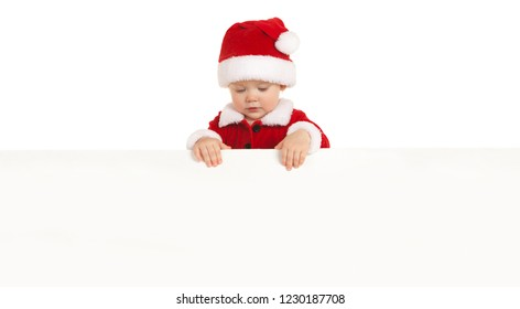 Happy santa baby with white blank board isolated on white. Small model in santa hat at studio holding paper poster. Christmas, xmas, winter concept. Santa girl looking at white blank board