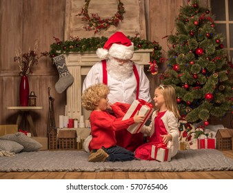 Happy Santa Claus and children sitting on carpet with Christmas gifts