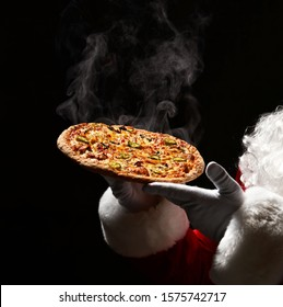 Happy Santa Claus hold big hot steaming pizza offering with copy space. New year and Merry Christmas fast food concept banner