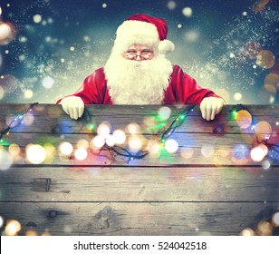 Happy Santa Claus holding blank advertisement wooden banner background with copy space. Smiling Santa Claus pointing in old wood blank sign. Christmas theme, sales, advertising