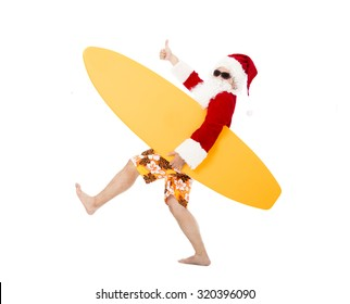 Happy Santa Claus holding surf board with thumb up