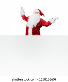 Happy Santa Claus jumping from behind the blank banner isolated on white background with copy space