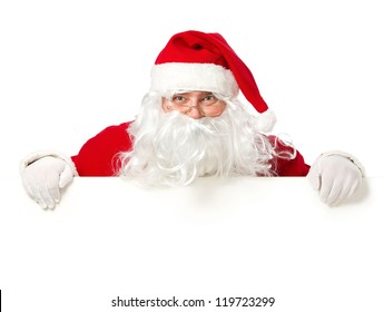 Happy Santa Claus looking out from behind the blank sign isolated on white background with copy space