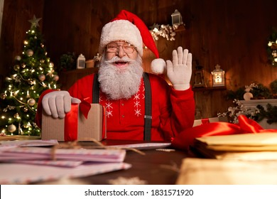 Happy Santa Claus, Saint Nicholas holding letter looking to camera, talking to webcam video calling or recording Happy New Year, Merry Christmas greetings on xmas eve sitting at table late at home.