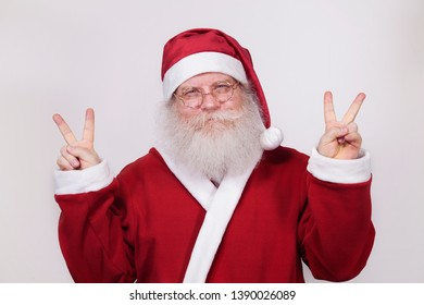 Happy Santa Claus showing a peace sign. Closeup portrait isolated on white background. Christmas theme.