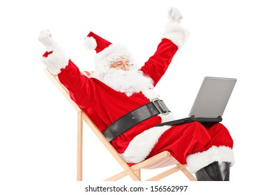 Happy Santa Claus sitting on a beach chair with laptop and gesturing happiness isolated on white background