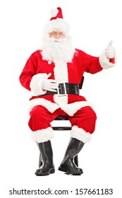 Happy Santa claus sitting on a wooden chair and giving a thumb up isolated on white background