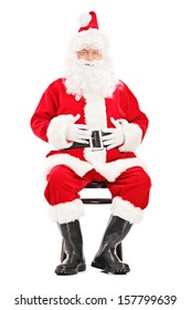 Happy Santa claus sitting on a wooden chair isolated on white background