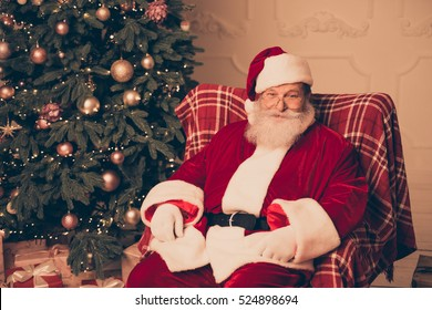 Happy Santa Claus sitting on chair in living room near christmas tree and presents wearing red costume