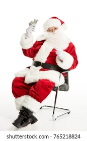 Happy Santa Claus sitting on chair and holding money isolated on white