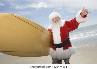 Happy Santa Claus with surf board on beach