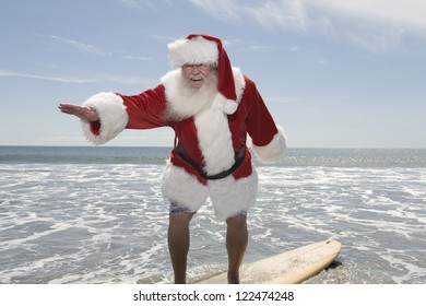 Happy Santa Claus surfing by the beach