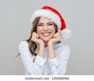 Happy Santa girl wearing Christmas hat. Close up face portrait.