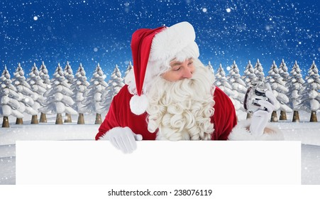 Happy santa holding alarm clock and sign against snowy landscape with fir trees