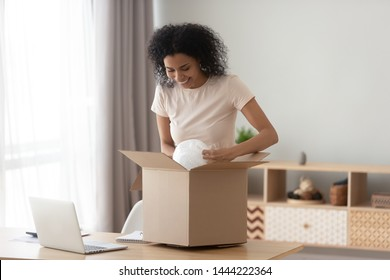 Happy satisfied black girl customer open parcel cardboard box at home, smiling african american woman consumer unpack package looking inside receive good purchase by postal shipping delivery concept