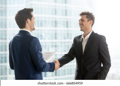 Happy satisfied business partners shaking hands after concluding contract for services on city building background, two smiling businessmen seal good deal, binding bargain with firm strong handshake